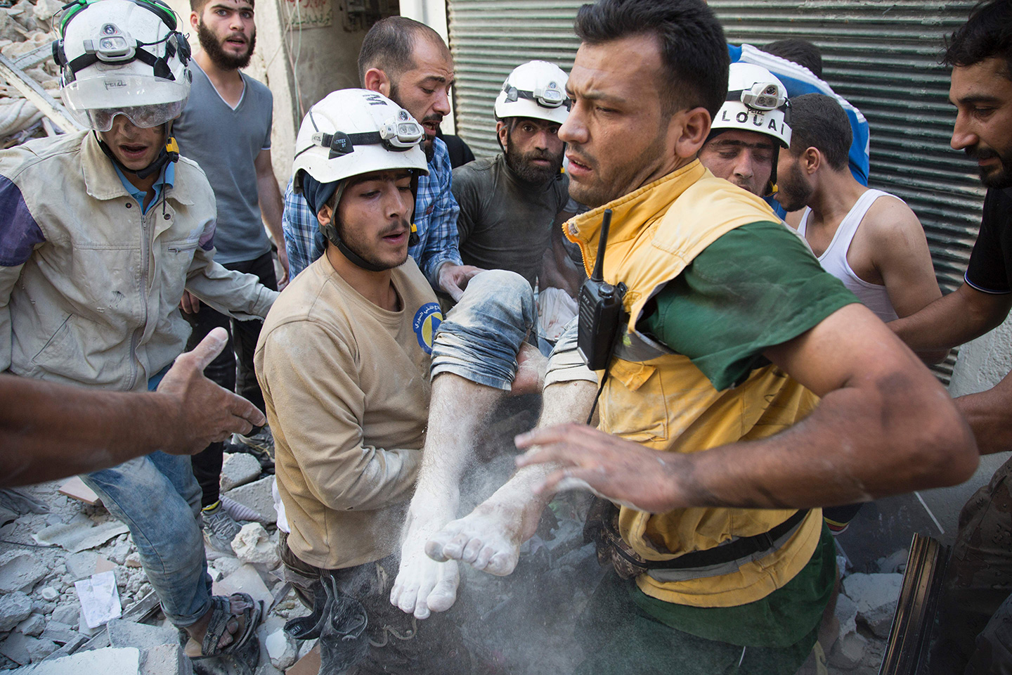 Syrian civil defense volunteers, known as the White Helmets, carry a body after digging