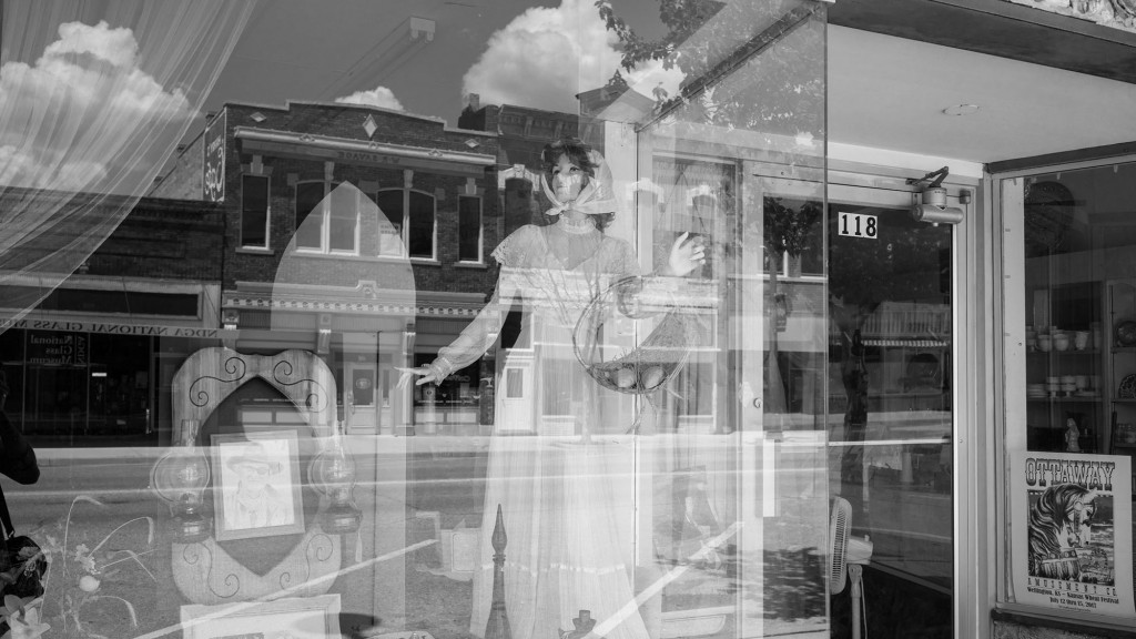 The reflection from a thrift shop in downtown. Wellington, KS. July 17, 2017.