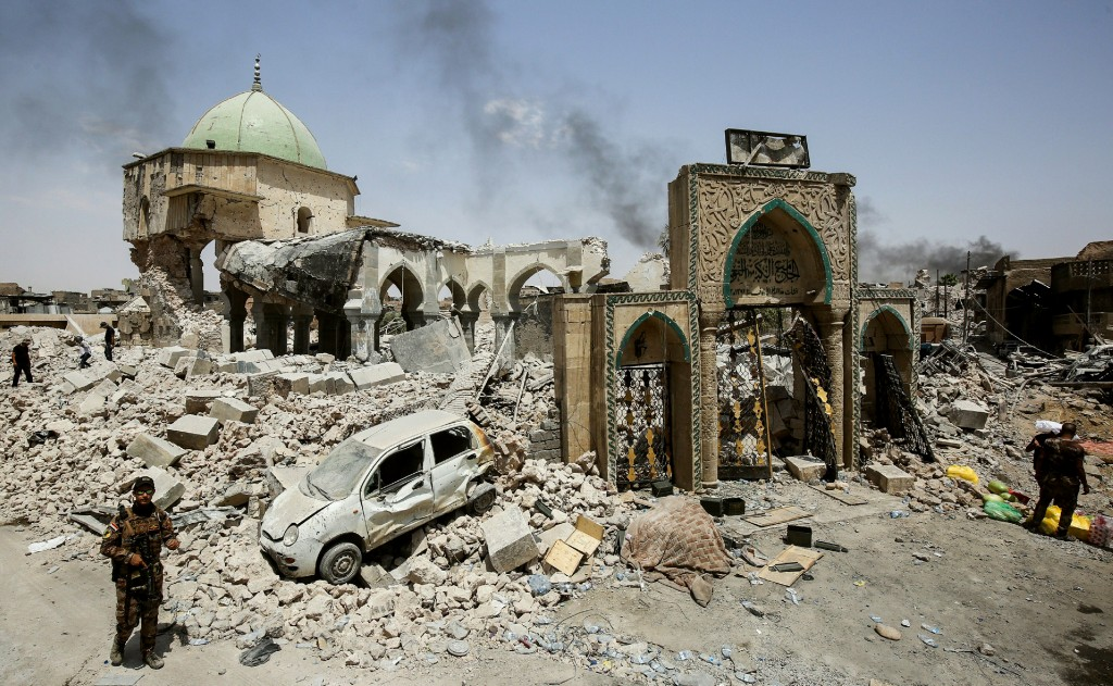 (COMBO) This combination of pictures created on January 09, 2018 shows (L) members of the Iraqi Counter-Terrorism Service (CTS) gathering outside the destroyed gate of the Al-Nuri Mosque in the Old City of Mosul on July 2, 2017, and a member of the security forces standing at the same place on January 8, 2018, six months after Iraqi forces seized the country's second city from Islamic State group jihadists. / AFP PHOTO / Ahmad al-Rubaye        (Photo credit should read AHMAD AL-RUBAYE/AFP/Getty Images)