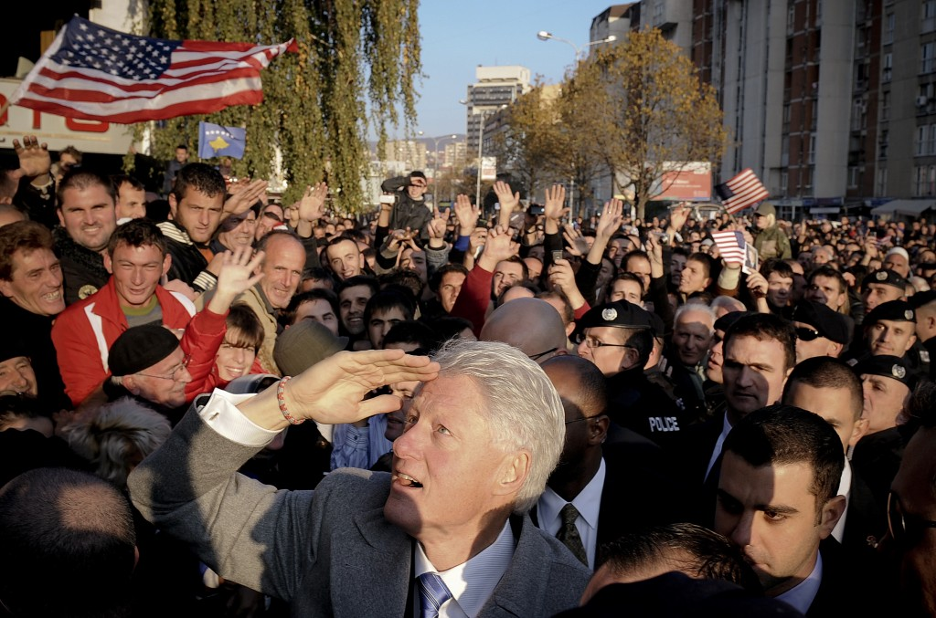 Former US President Bill Clinton (C, front) gestures as he greets Kosovo citizens during his visit in Pristina on November 1, 2009. Kosovo Albanians, who admire Clinton because of his role in the 1999 NATO bombings of then Yugoslavian President Slobodan Milosevic, honoured him by erecting a three-metre (10-feet) tall monument on a Pristina boulevard already named after him. AFP PHOTO/ARMEND NIMANI (Photo credit should read Armend Nimani/AFP/Getty Images)
