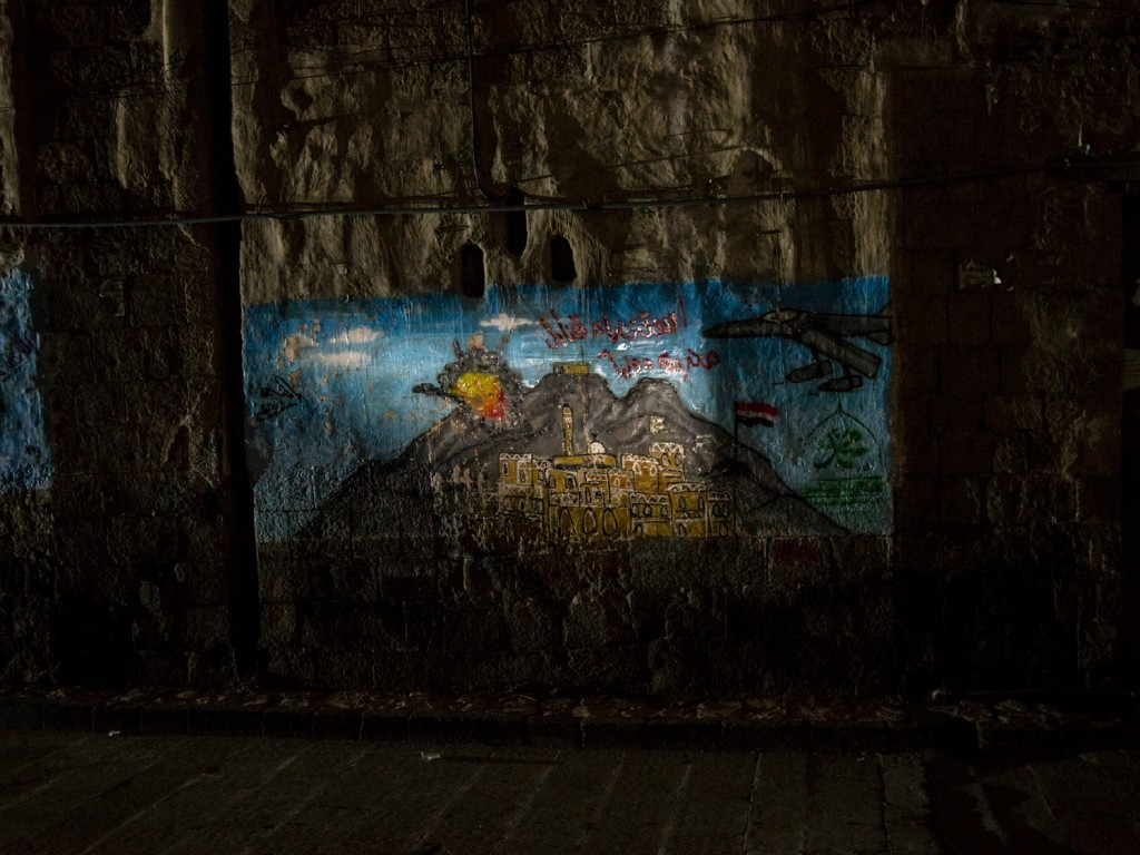 Light from a corner store shines on a mural depicting airstrikes in the Old City on April 30 in Sana'a, Yemen.