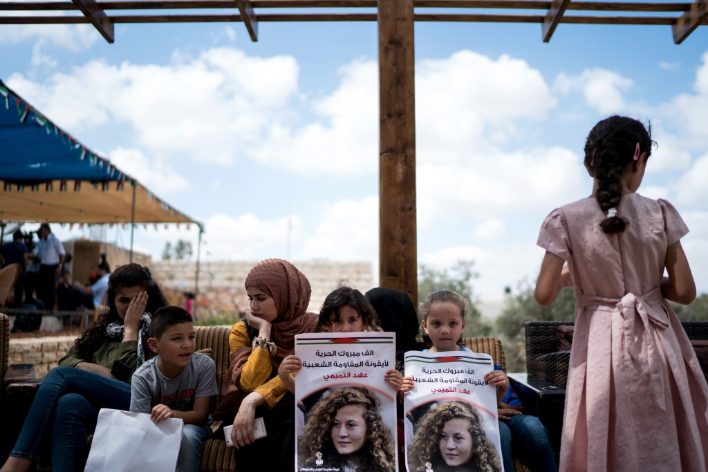 young girls hold posters of Ahed at her house on July 29, 2018 as they wait for her to arrive