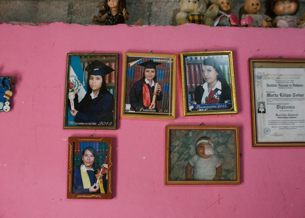 Photos of the Tobar family hang on the wall of their home in Jutiapa, El Salvador. Yanci Tobar, left, is currently seeking asylum in the United States.