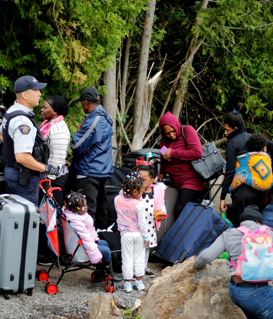 A Royal Canadian Mounted Police (RCMP) officer announces to a group of asylum seekers that identified themselves as from Haiti, that they will be crossing illegally into Canada as they wait in line to to enter at the US-Canada border in Champlain, New York August 7, 2017. REUTERS/Christinne Muschi - RC13C4B37710