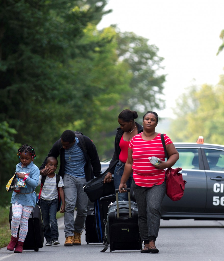 A family that stated they are from Haiti walk to the US-Canada border to cross into Canada from Champlain, New York, U.S. August 11, 2017. REUTERS/Christinne Muschi - RC15A22CDE70