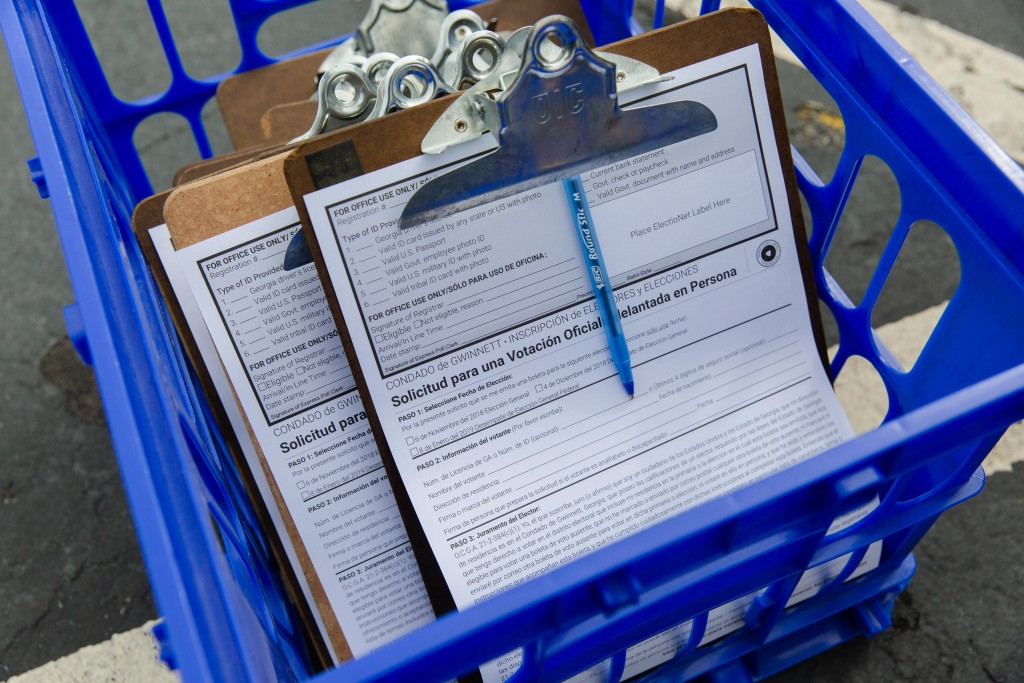 Paperwork, printed in both English and Spanish, waits for voters sits in a basket at the at the Gwinnett County (Ga.) Voter Registrations and Elections Office in Lawrenceville, Ga., on Wednesday, Oct. 17, 2018. on Wednesday, Oct. 17, 2018. Photo by Kevin D. Liles for The Intercept