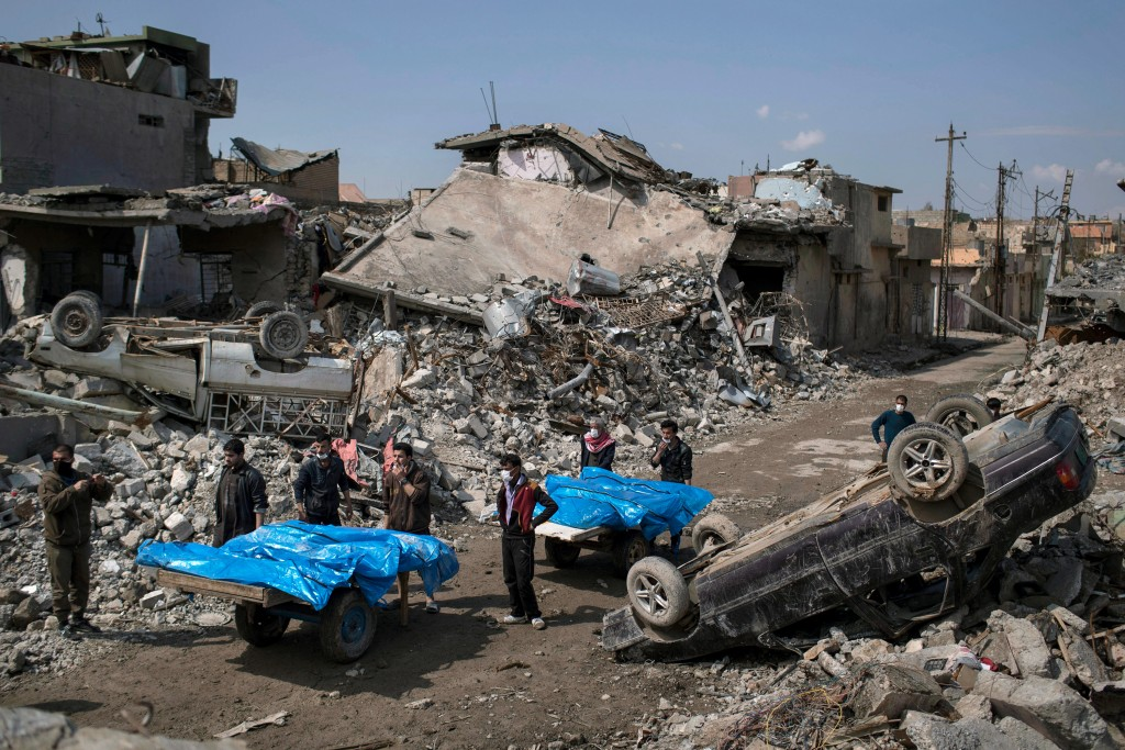 Residents carry the body of several people killed during fights between Iraq security forces and Islamic State on the western side of Mosul, Iraq, Friday, March 24, 2017. Residents of the Iraqi city's neighborhood known as Mosul Jidideh at the scene say that scores of residents are believed to have been killed by airstrikes that hit a cluster of homes in the area earlier this month (AP Photo/Felipe Dana)