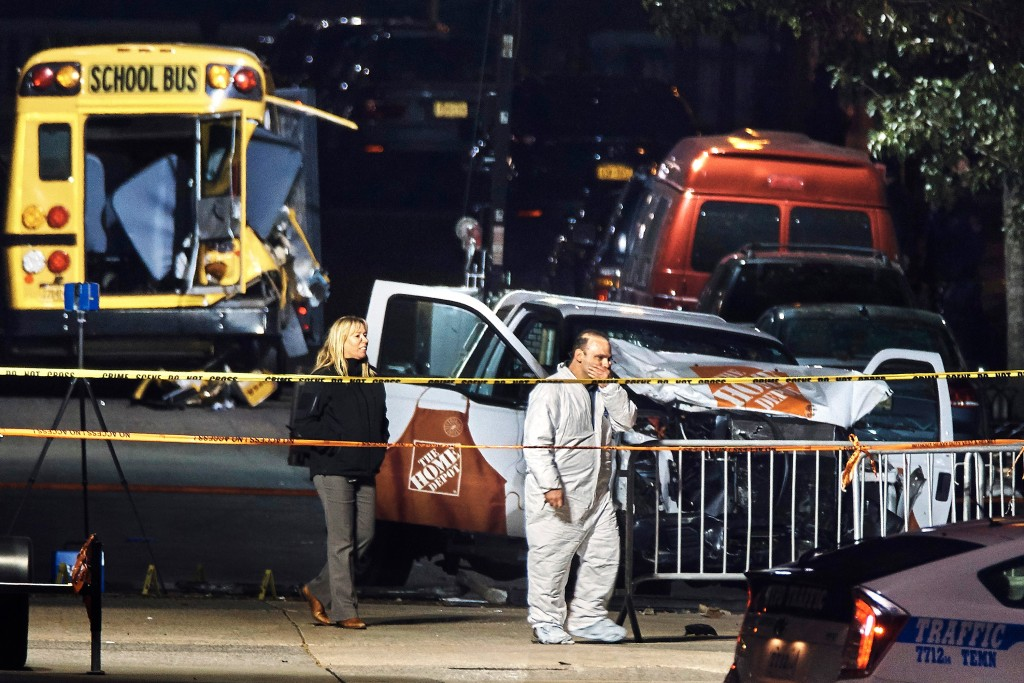 Police work near a damaged Home Depot truck Wednesday, Nov. 1, 2017, after a motorist drove onto a bike path Tuesday near the World Trade Center memorial, striking and killing several people, in New York. (AP Photo/Andres Kudacki)