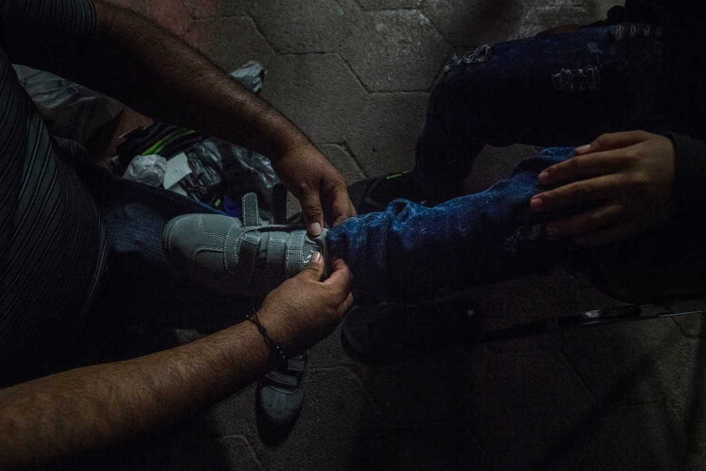 Volunteer Elías Cantú puts on a new pair of shoes for a teenager asylum seeker waiting near the international bridge in Matamoros, Tamaulipas on Nov. 5, 2018. Photo: Verónica G. Cárdenas for The Intercept