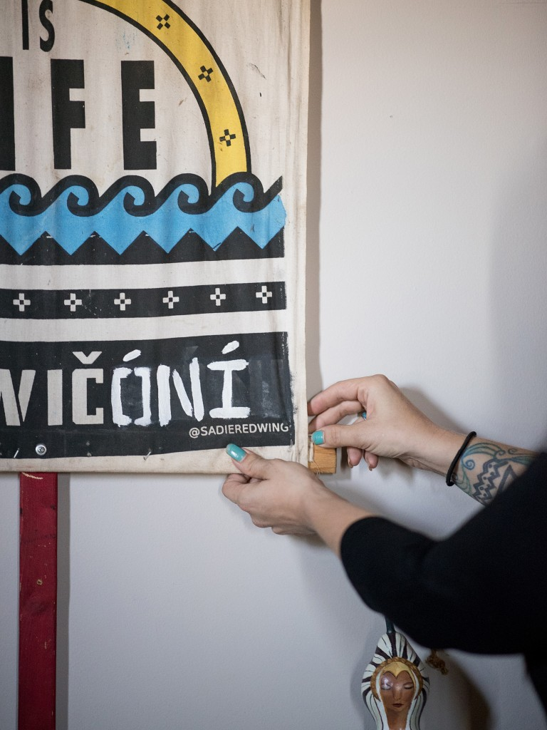 "CAPTION: Jen Mendoza, an anti-pipeline activist who was affected by the surveillance actions of security contractor TigerSwan, adjusts a ""Water if Life"" banner that was at Standing Rock in her room at her home in Cincinnati, OH on Sunday, September 30, 2018. (Emma Joy Howells for The Intercept)"
