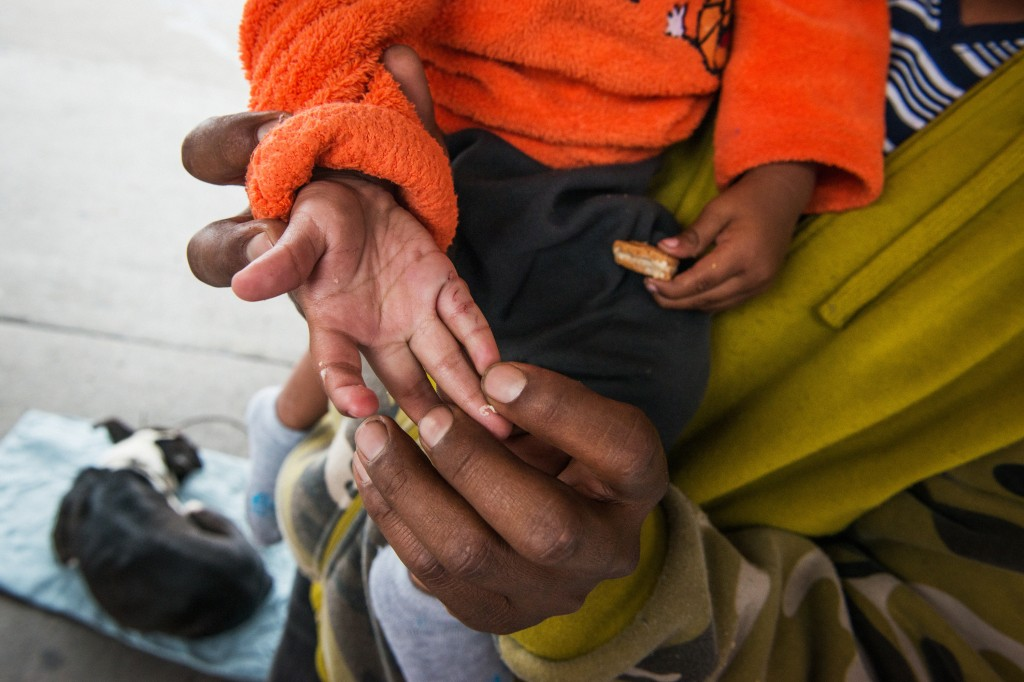 In the foreground, Eric holds open the palm of his son's hand, revealing four bite marks from a rat found in the tent shared with his wife Oneida, eldest son Julian and a friend the night before on December 6, 2018. La Negra, a dog adopted by one of the fellow Hunger Strikers while on the caravan, sleeps in the background.