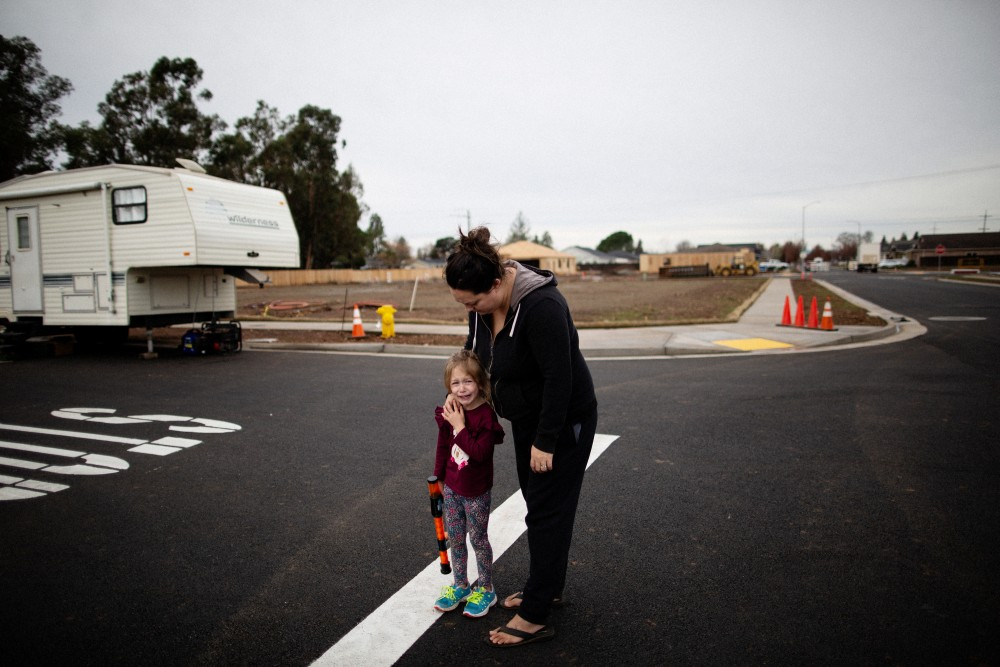 "Michelle's Teixeira comforts her 4 year old daughter who had been playing with other kids who are living in trailers on undeveloped lots after their homes were burned by the Camp Fire, Chico, California, December 21st, 2018. Michelle Teixeira is living in a 300 square foot trailer with her husband, her father, two daughters, and four dogs. Her husband's boss owns a residential development made up of 36 empty lots, where the Teixeiras and five other families have made camp, calling themselves the ""trailer treasures."" They're all refugees from the Camp wildfire, which leveled Paradise, California, killing 86 people, including many retirees.Talia Herman for The Intercept"