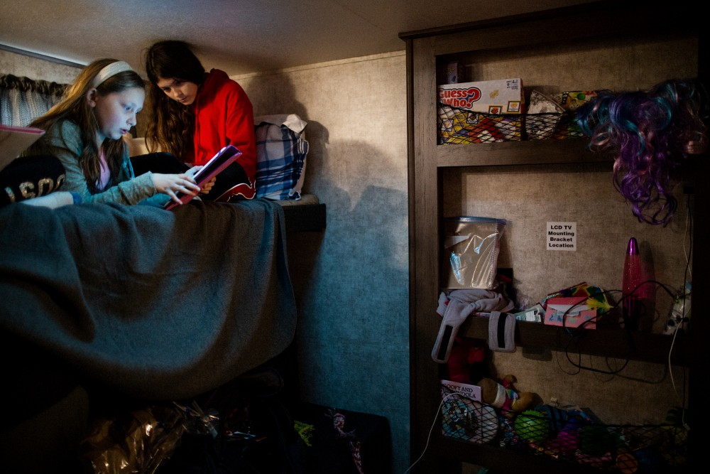 "Michelle's Teixeira's 14 year old daughter (on the right) playing on her bed in their new trailer with a kid who also lost her home to the Camp Fire, Chico, California, December 21st, 2018. Michelle Teixeira is living in a 300 square foot trailer with her husband, her father, two daughters, and four dogs. Her husband's boss owns a residential development made up of 36 empty lots, where the Teixeiras and five other families have made camp, calling themselves the ""trailer treasures."" They're all refugees from the Camp wildfire, which leveled Paradise, California, killing 86 people, including many retirees.Talia Herman for The Intercept"