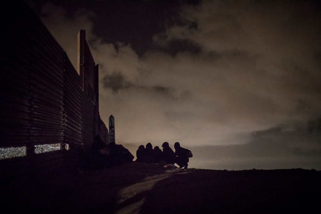 Asylum seekers from Honduras hide next to the border wall that divides U.S. and Mexico to avoid being detected by the border police before trying to jump and enter the U.S. from Tijuana, Mexico, Dec. 30, 2018. (© Santi Palacios)