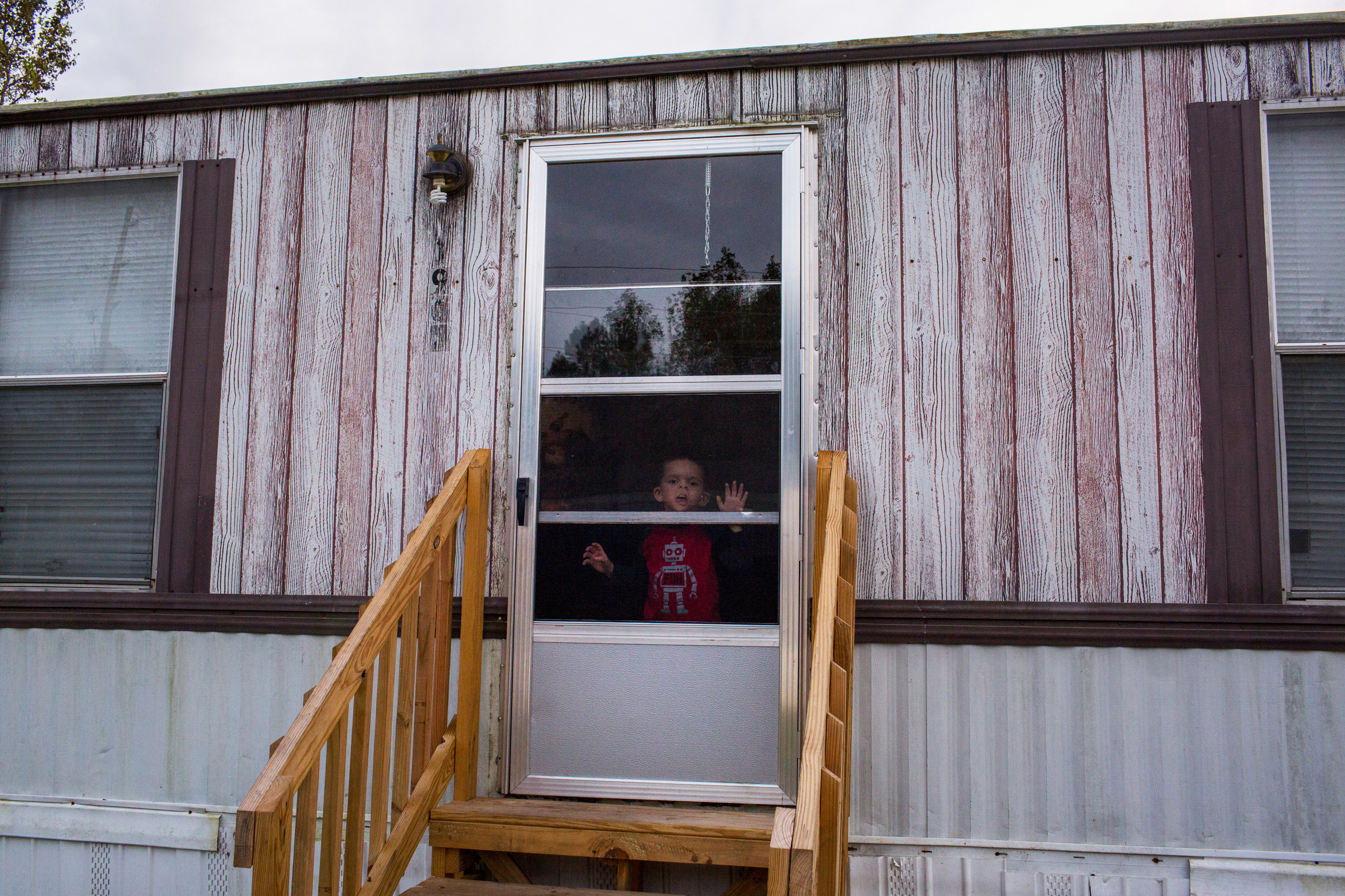 October 23, 2018. Lumberton NC. Jamie Brewer's son peers at the door of their trailer near Alamac road.