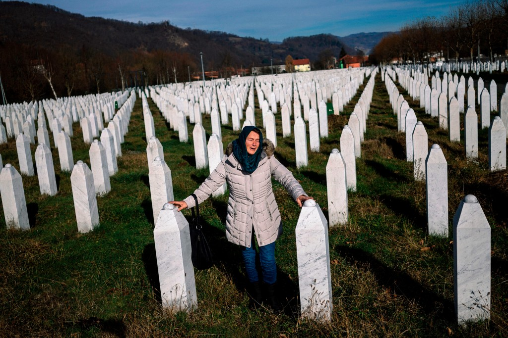 TOPSHOT - A woman mourns over a relative's grave at the memorial centre of Potocari near Srebrenica on November 22, 2017.United Nations judges on November 22, 2017 sentenced former Bosnian Serbian commander Ratko Mladic to life imprisonment after finding him guilty of genocide and war crimes in the brutal Balkans conflicts over two decades ago.