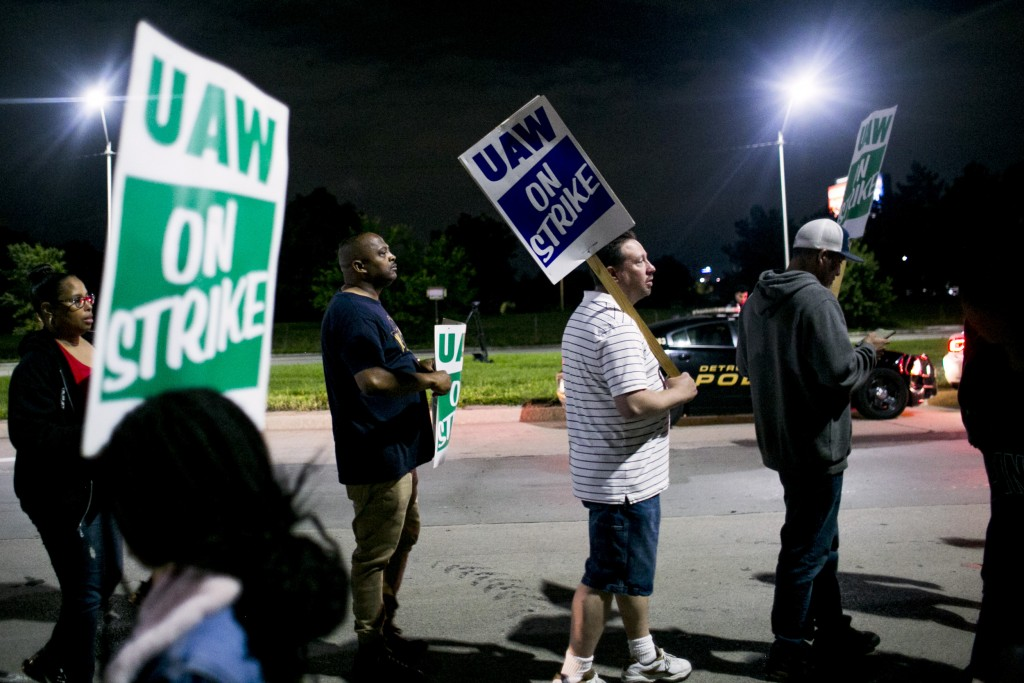 "Demonstrators hold signs reading ""UAW On Strike"" during a United Auto Workers (UAW) strike outside the General Motors Co. Hamtramck assembly plant in Detroit, Michigan, U.S., on Monday Sept. 16, 2019. General Motors Co. workers called their first strike in 12 years, halting work at dozens of facilities across the U.S. in a clash over jobs, pay and benefits. Photographer: Anthony Lanzilote/Bloomberg via Getty Images"