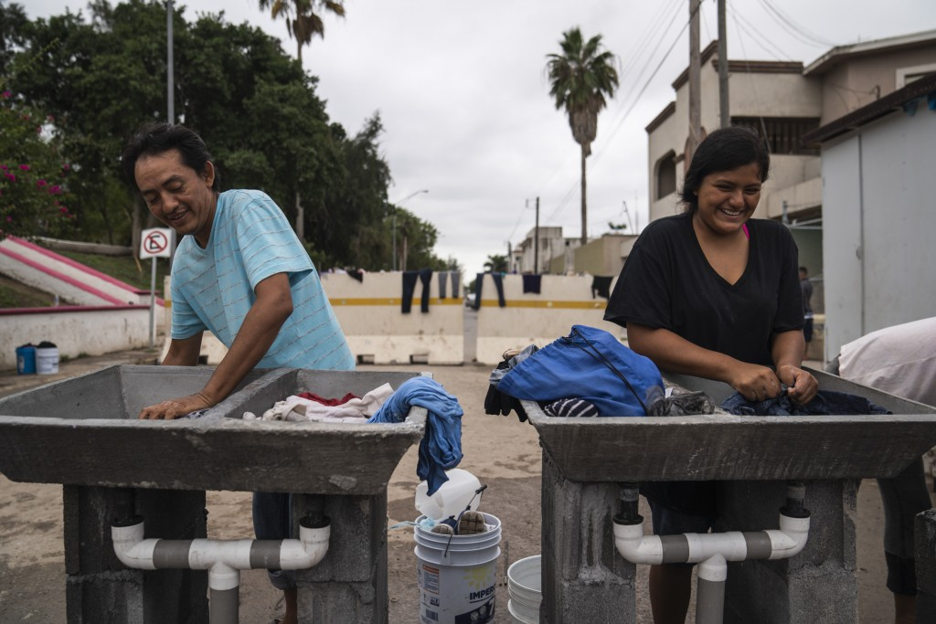 "Miguel, 44, washes clothes with his daughter Julissa, 15,  in an encampment where they live near the Gateway International Bridge on Oct. 22, 2019 in Matamoros, Mexico. They have been living in the encampment for two months after they were sent back under the Migrant Protection Protocols, MPP, also referred to as ""Remain in Mexico"" program."