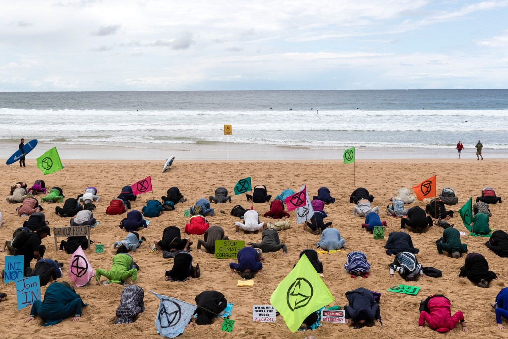 "SYDNEY, AUSTRALIA - OCTOBER 11: Extinction Rebellion activists gather on Manly beach and bury their heads in the sand on October 11, 2019 in Sydney, Australia. The event was organised as part of Extinction Rebellion's global ""Week Of Action"" in 60 cities across the world to bring attention to climate change and push governments to declare a climate emergency. (Photo by Brook Mitchell/Getty Images)"