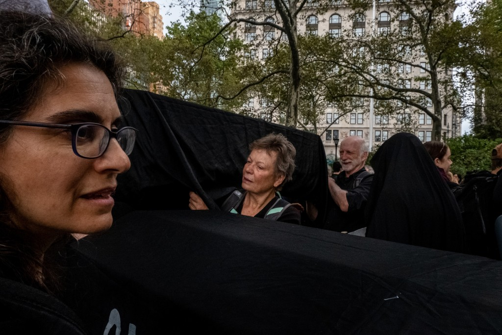 "NEW YORK, NEW YORK– OCTOBER 7, 2019: The environmental group Extinction Rebellion (commonly referred to as XR) gather in Battery Park before leading a group of protesters in marching and action in Manhattan on Monday. Numerous members were arrested while blocking roads and performing ""die-ins."""