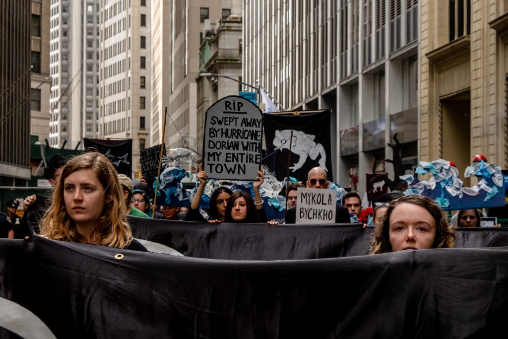 NEW YORK, NEW YORK– OCTOBER 7, 2019: The environmental group Extinction Rebellion (commonly referred to as XR) stage a die-in  on the street in front of the New York Stock Exchange. XR lead a group of protesters in marching and action in Manhattan on Monday. Numerous members were arrested.