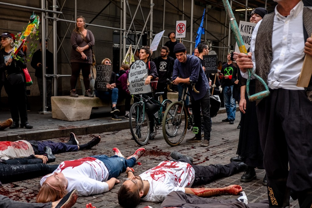 NEW YORK, NEW YORK– OCTOBER 7, 2019: The environmental group Extinction Rebellion (commonly referred to as XR) stages a die-in  on the street in front of the New York Stock Exchange. XR lead a group of protesters in marching and action in Manhattan on Monday. Numerous members were arrested.