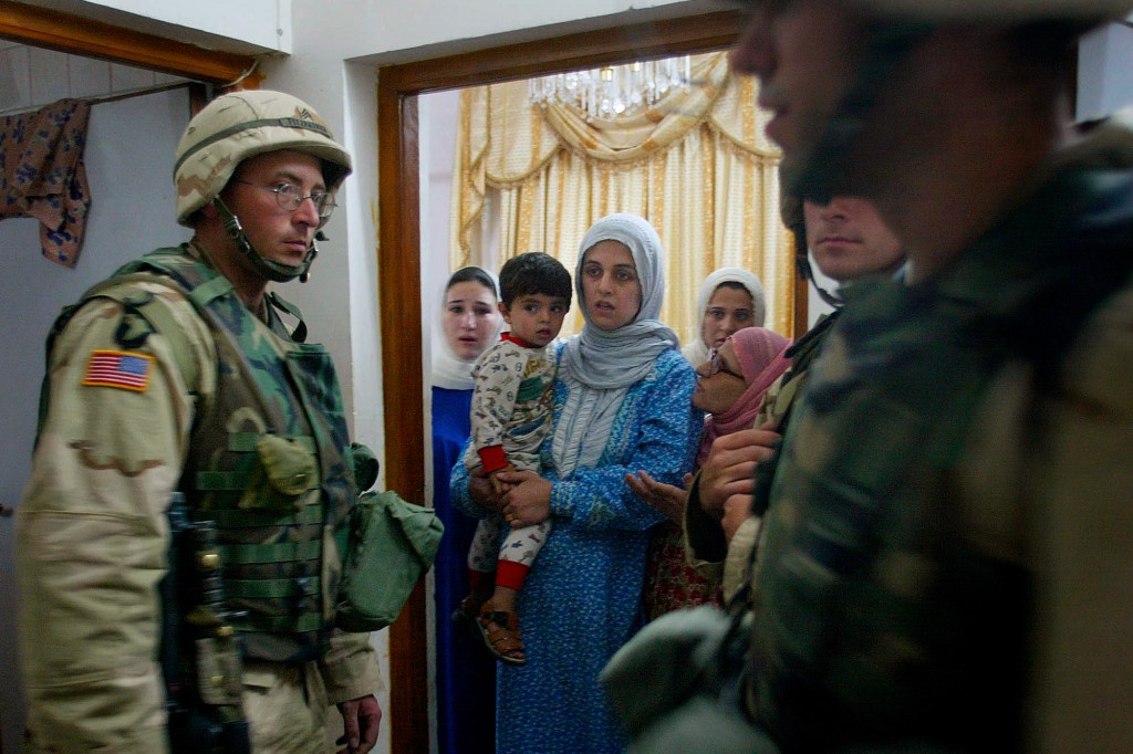 Women of the household watch as soldiers of the 4th Infantry Division arrest a man, who the commander of the 1st Brigade identified as a  prominent Ba'ath Party member in Tikrit, Iraq, Wednesday April 30, 2003.  Heavily armed troops of the 4th Infantry Division raided a house in Saddam Hussein's hometown late Wednesday and arrested a local Baath Party official accused of trying to run a ``shadow regime'' opposing the Americans. His two sons were also arrested. (AP Photo/Saurabh Das)