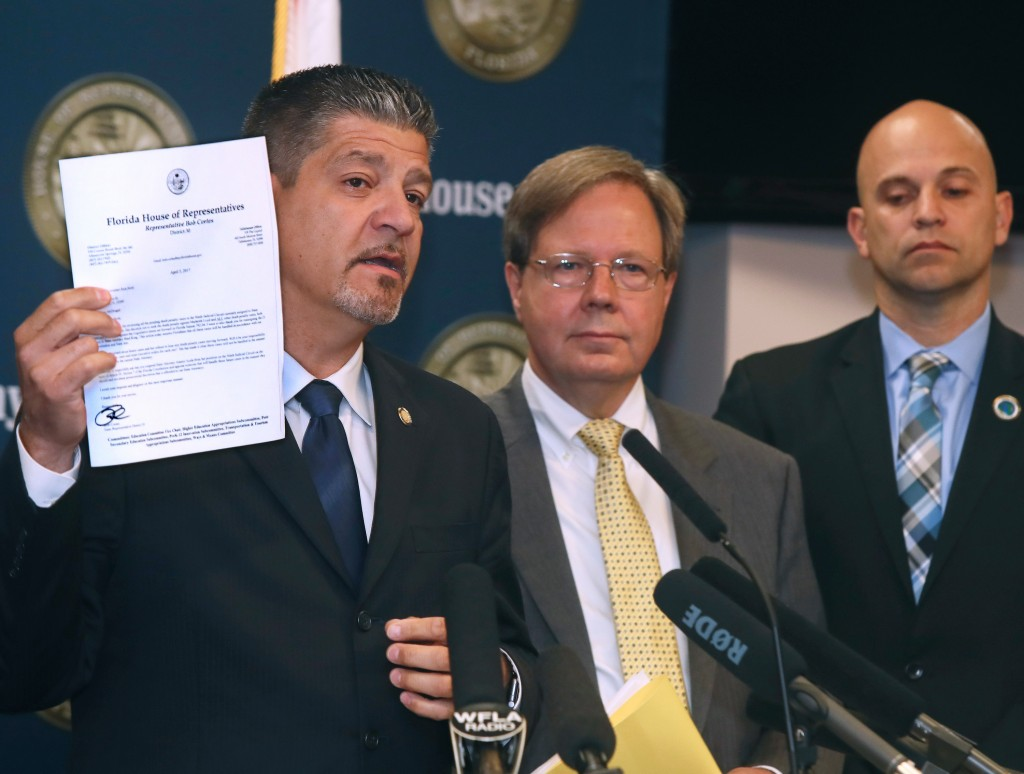Florida Rep. Bob Cortes, R-Altamonte Springs, holds up a letter he sent Gov. Rick Scott in support of a reassignment of 21 first-degree murder cases from State Attorney Aramis Ayala's office during a press conference Tuesday, April 4, 2017, in the Florida House in Tallahassee, Fla. Behind Cortes are Rep. Scott Plakon, R-Longwood and Rep. Rene Plasencia, R-Orlando. Cortes is calling for Ayala to either resign or be removed from office by Gov. Scott. (AP Photo/Phil Sears)