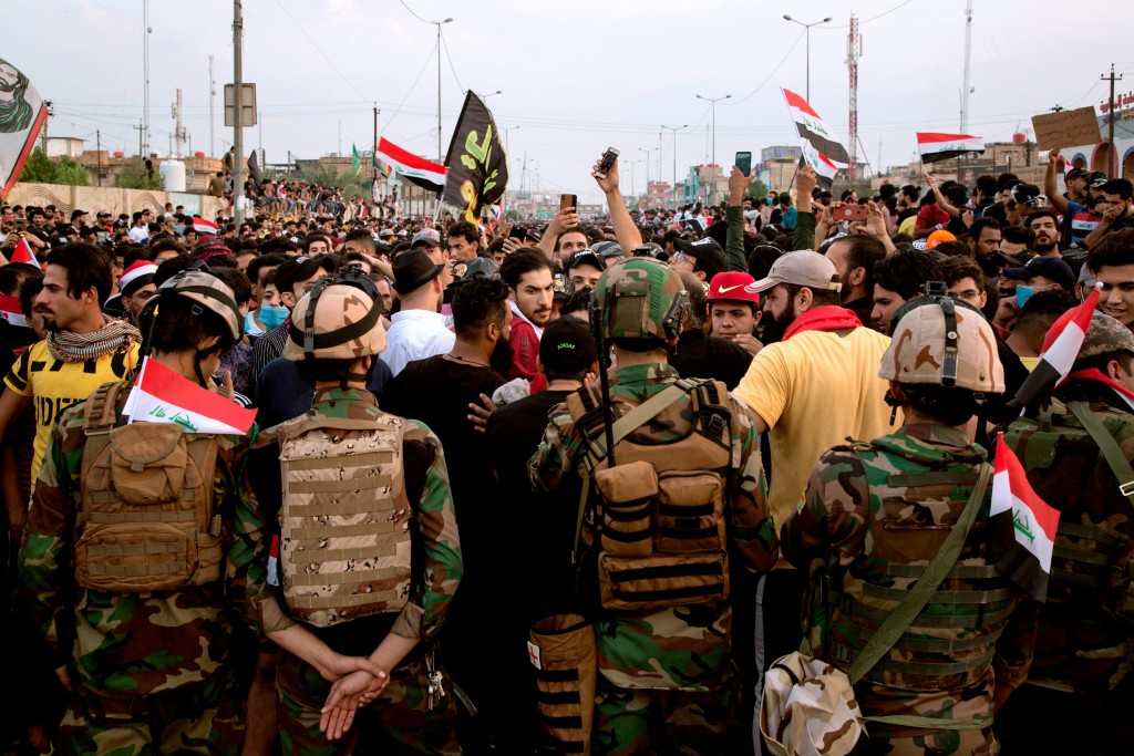 Iraqi soldiers surround anti-government protesters outside the local government headquarters in the southern city of Basra on October 28, 2019. - The Iraqi army announced it would impose an overnight curfew in the capital as students and schoolchildren joined spreading protests to demand an overhaul of the government. Swathes of Iraq have been engulfed by demonstrations over unemployment and corruption this month that have evolved into demands for regime change. (Photo by - / AFP) (Photo by -/AFP via Getty Images)