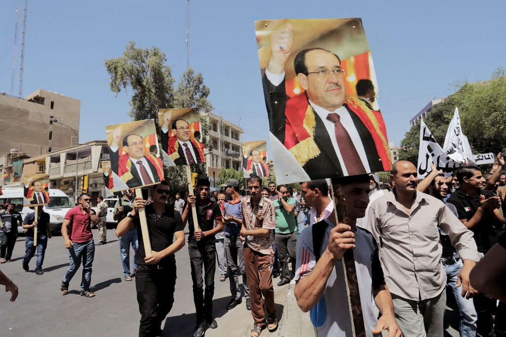 BAGHDAD, IRAQ - AUGUST 13:  Iraqis carry portraits of incumbent Iraqi Prime Minister Nouri al-Maliki as they gather in support of him at the Firdos Square in Baghdad, Iraq on August 13, 2014. Iraqi citizens chant slogans during a protest of Shiite lawmaker Haider al-Abadi and his candidate to lead the government in Iraq. (Photo by Stringer/Anadolu Agency/Getty Images)