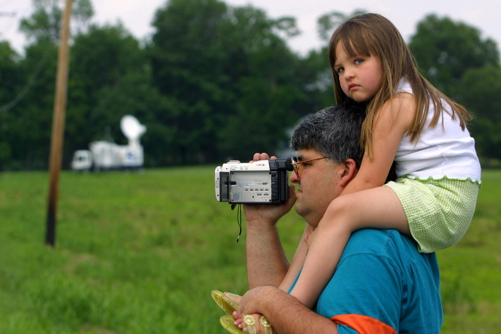 Dean Spiegel from Indianapolis, Indiana carries his 4-year-old daughter Sophia on his shoulders June 9, 2001 as he videotapes activities near the entrance to the grounds of the U.S. Federal Prison in Terre Haute, Indiana. Convicted Oklahoma City bomber Timothy McVeigh is scheduled to be executed at the prison on June 11, 2001. (Photo by Tim Boyle/Getty Images)
