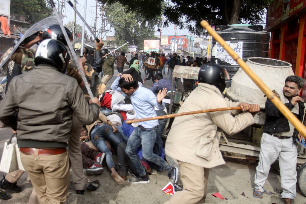 TOPSHOT - In this photo taken on December 19, 2019 police beat protesters with sticks during a demonstration against India's new citizenship law in Lucknow. - Indians defied bans on assembly on December 19 in cities nationwide as anger swells against a citizenship law seen as discriminatory against Muslims, following days of protests, clashes and riots that have left six dead. (Photo by STR / AFP) (Photo by STR/AFP via Getty Images)