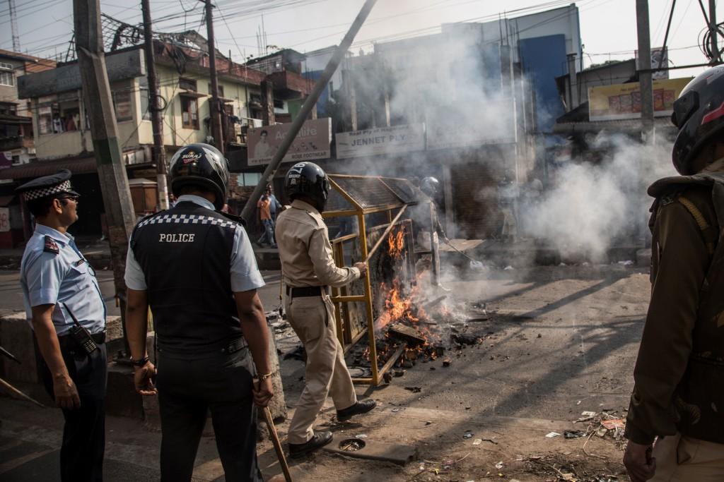 Police officials remove burning barricade on a street in Guwahati, Assam, Dec. 12, 2019.