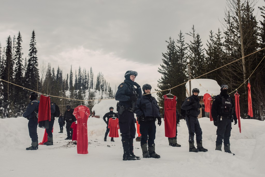 Royal Canadian Mounted Police stage among red dresses as they prepare to enforce Coastal GasLink's injunction at Unist'ot'en Healing Centre near Houston, B.C. on Monday, February 10, 2020. Amber Bracken