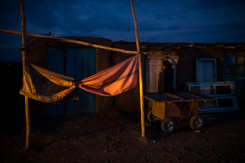 A shopkeeper closes up his store at dusk in the small bazaar inside the Shahrak-e Sabz IDP camp, or informal settlement, on the outskirts of Herat City.
