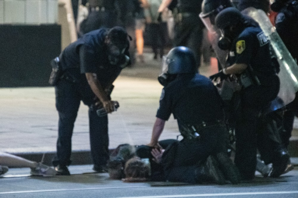 Protestor Caylee Arnold is pepper sprayed in the face by a Detroit police officer after being detained around midnight of August 23, 2020 when the activist organization Detroit Will Breathe held a small scale occupation of Woodward Avenue in downtown Detroit, Michigan.