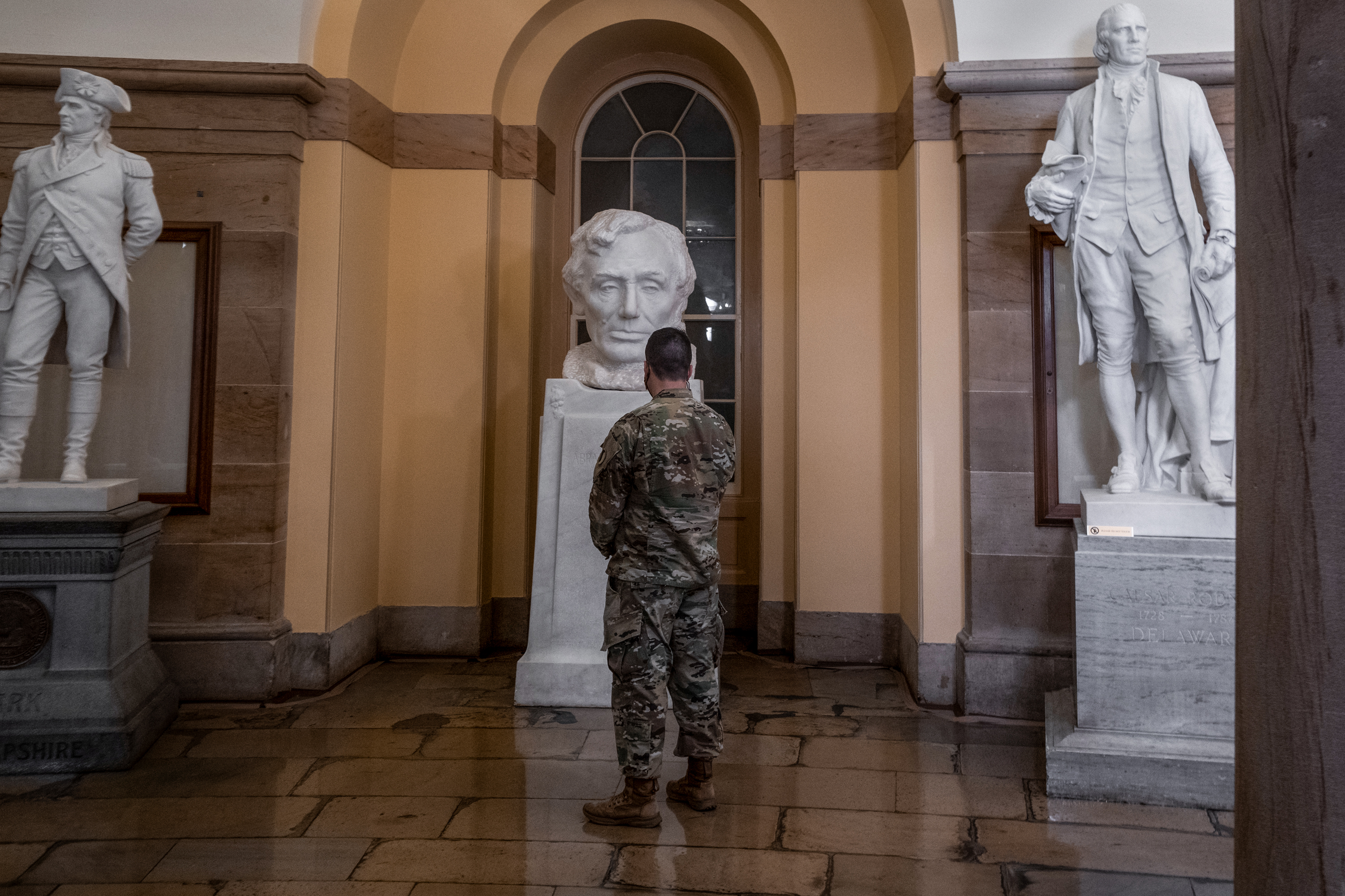 A National Guard soldier looks at Lincoln in the statutory in the capitol building in Washington DC.