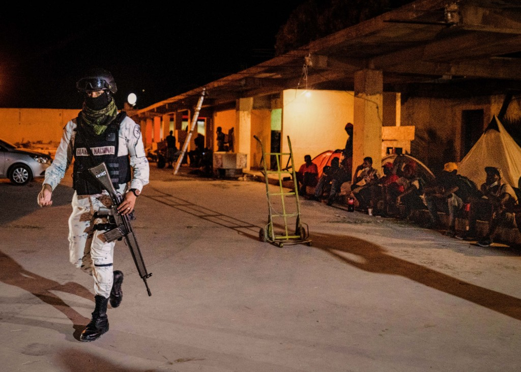 A member of the National Guard monitors a shelter for migrants, who are mostly Haitians, that had been under the Acuña - Del Rio International Bridge to turn themselves in to Border Patrol, that are now in Acuña, Mexico on Sept. 24, 2021. Verónica G. Cárdenas for The Intercept
