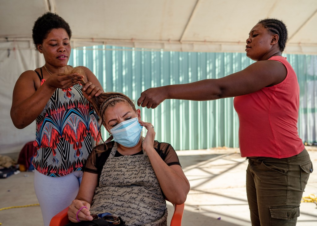 Christela, 28, left, a Haitian migrant, does the hair of volunteer Celia Guerra, 52, as Veloude, 28, right, fixes Celia's hair at a migrant shelter in Acuña, Mexico on Sept. 25, 2021.  Verónica G. Cárdenas for The Intercept